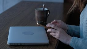 Female hands holding smartphone in coffee shop with laptop on the background. Pan right - Female hands holding smartphone in coffee shop with laptop on the stock video footage