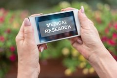 Medical research concept on a smartphone. Female hands holding a smartphone with medical research concept stock photos