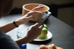 Female hands holding smartphone and showing photos. To man, young women demonstrating gallery on phone during breakfast, looking for photo, hand view close up royalty free stock photos