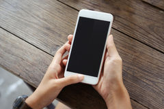 Female hands holding smartphone. Top view : young woman sitting at a table with a coffee using mobile phone Stock Photo