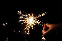 Female hands holding sparkler with night background Stock Photos