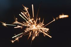 Female hands holding sparkler with night background Stock Image