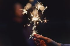 Female hands holding sparkler with night background Royalty Free Stock Images
