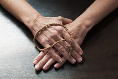 Female hands holding a symbolic cross praying Royalty Free Stock Photography
