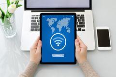 Female hands holding tablet with app wifi connect and laptop. Female hands holding tablet with app wifi connect on the screen laptop and phone background royalty free stock images