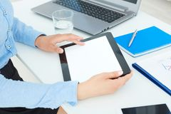 Female hands holding tablet with blank screen in office background. stock image