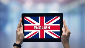 Female hands holding tablet with English word against Britain flag, online app. Stock footage stock video