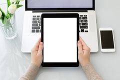 Female hands holding tablet with isolated screen laptop and phon Royalty Free Stock Photos