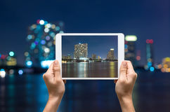Female hands holding tablet taking pictures cityscape Modern bui Stock Photography