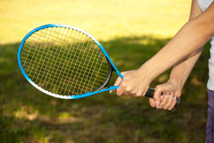 Female hands holding a tennis racket. Close up of female hands holding a tennis racket stock photography