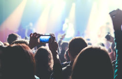Female hands holding their smartphone and photographing rock con Stock Photos