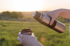 Travelling hiking backpacking sunset tourism. Female hands holding thermal flask with cup on the sunset. Concept of the travelling, backpacking, hiking, outdoor Stock Photos