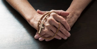 Female hands holding tight a Christian cross Royalty Free Stock Photography
