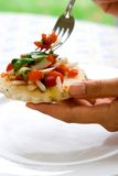 Female hands holding tomato salad on toasted bread. Serving some on a fork royalty free stock images