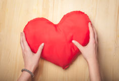 Female hands holding toy red heart on wooden table Stock Image