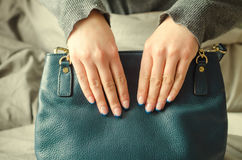 Female hands holding turquoise handbag on gray background. royalty free stock photos