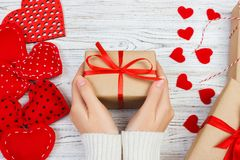 Female hands holding Valentines day gift above wooden table with red hearts. Top view. Xmas gift wrapping Stock Photo