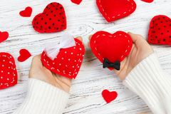 Female hands holding Valentines day heart above wooden table. Top view. Xmas gift wrapping.  royalty free stock image