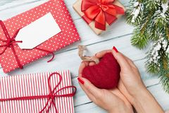 Female hands holding Valentines day heart. Above wooden table. Top view. Xmas gift wrapping stock photos
