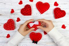 Female hands holding Valentines day heart above wooden table. Top view. Xmas gift wrapping.  stock photography