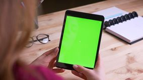 Female hands holding vertically tablet with green chroma screen on office background. Female hands holding vertically tablet with green chroma screen on office stock video