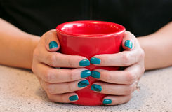 Female Hands holding a warm red cup of coffee. Female Hands with pretty nails holding a warm coffee mug Stock Photography