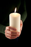 Female hands holding a white candle, shallow DOF Stock Photos