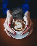 Female hands holding white cup with hot coffee. Close up of female caucasian hands holding white cup with hot coffee Royalty Free Stock Photo