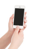 Female hands holding white modern smart phone and pressing button by the thumb royalty free stock images