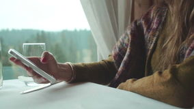 Female hands holding a white phone at the table. Close up hands of woman typing text message on smart phone in a cafe. Young woman sitting at a table with glass stock video footage