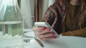 Female hands holding a white phone at the table. Close up hands of woman typing text message on smart phone in a cafe. Young woman sitting at a table with glass stock footage