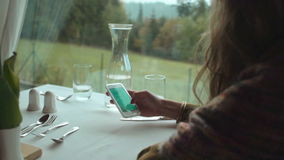Female hands holding a white phone at the table. Close up hands of woman typing text message on smart phone in a cafe. Young woman sitting at a table with glass stock video