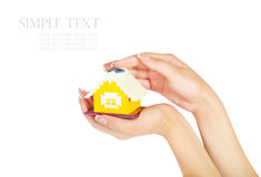 Female hands holding a yellow house isolated on white background Royalty Free Stock Image