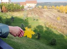 Female hands are holding a yellow maple leaf against the background of the autumn landscape in the distance. Signs of autumn royalty free stock photo