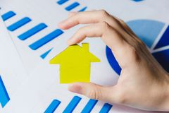 Female Hands Holding Yellow Paper House, Homeless Housing Shelter and Real Estate , Family House Insurance Concept. Royalty Free Stock Photo