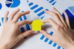 Female Hands Holding Yellow Paper House, Homeless Housing Shelter and Real Estate , Family House Insurance Concept. Stock Photography