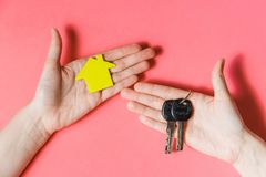 Female Hands Holding Yellow Paper House and Keys, Housing Shelter and Real Estate , Family House Insurance Concept. Royalty Free Stock Photo