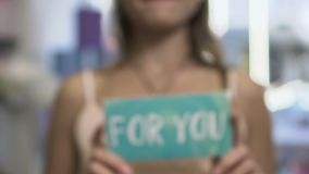 Text on card `for you`. Female hands holds a card with text for you. Female demonstrate a card in close-up on camera. She holds a card so close and then take off stock video footage