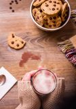 Female hands with hot drink and chocolate cookies Royalty Free Stock Photography
