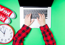 Female hands and huge clock with gumshoes near laptop Stock Photography