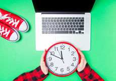 Female hands and huge clock with gumshoes near laptop Royalty Free Stock Photos