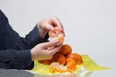 Female hands husk tangerines. Well-groomed female hands with manicure husk tangerines stock photos