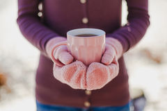 Female Hands In Pink Mittens Holding Cup With Hot Tea Or Coffee. Close Up Royalty Free Stock Photo