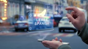 Female hands interact HUD hologram Learn Spanish. Female hands on the street interact with a HUD hologram with text Learn Spanish. Woman uses the holographic stock video