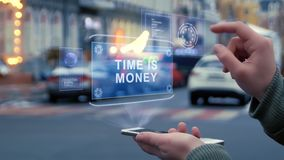 Female hands interact HUD hologram Time is money. Female hands on street interact with HUD hologram with text Time is money. Woman uses the holographic stock video footage