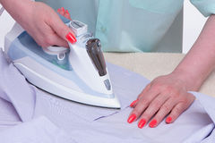 Female hands iron clothes Royalty Free Stock Image