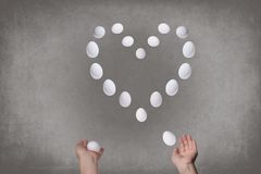 Female hands juggle eggs in the form of Valentine`s heart . Food  concept. Female hands juggle eggs in the form of Valentine`s heart . Food and relations Stock Photography