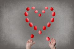 Female hands juggle eggs in the form of Valentine`s heart . Food  concept. Female hands juggle eggs in the form of Valentine`s heart . Food and relations Stock Images