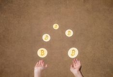 Female hands juggle of glowing coin crypto currency of bitcoin on gold background. Symbol BTC Stock Photography