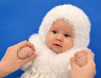 Female hands keep the baby in a New Year's suit of the Snowflake. On a blue background stock images